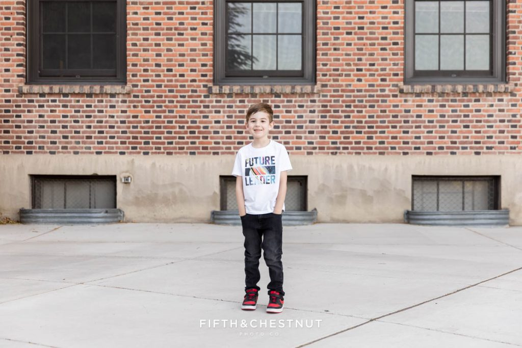 A young boy standing with his hands in his pockets in front of a brick building at UNR for his Reno child Portraits