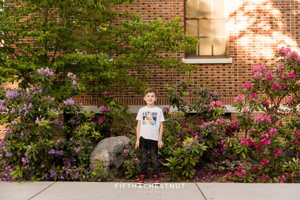 A 6 year old boy stands in between beautiful flowers at UNR for his 6 year portraits