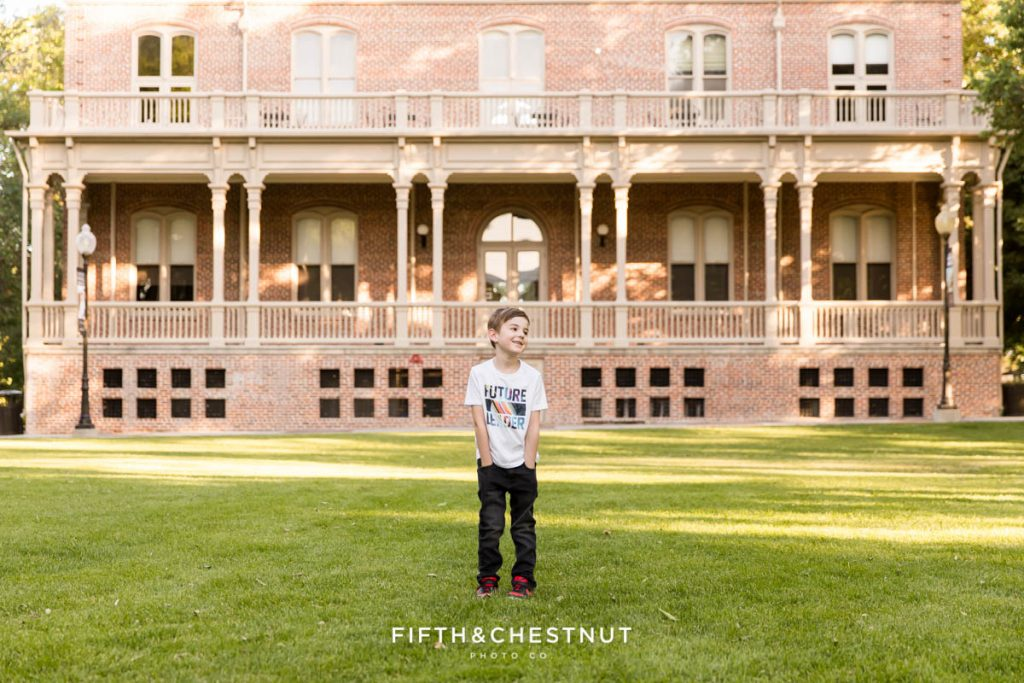 """A 6 year old boy stands with his hands in his pockets wearing a shirt that says """"Future Leader"""" in front of the Morrill Hall UNR alumni building on the south quad on a warm spring day"""