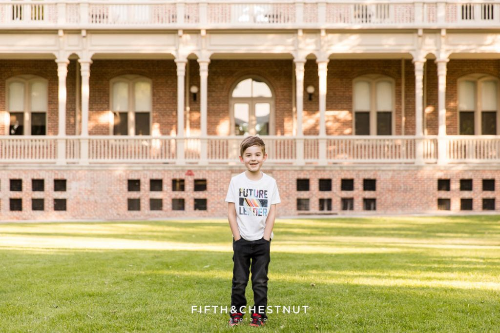 """A 6 year old boy stands with his hands in his pockets wearing a shirt that says """"Future Leader"""" in front of the Morrill Hall UNR alumni building on the south quad for child portraits by Reno Child Photographer"""