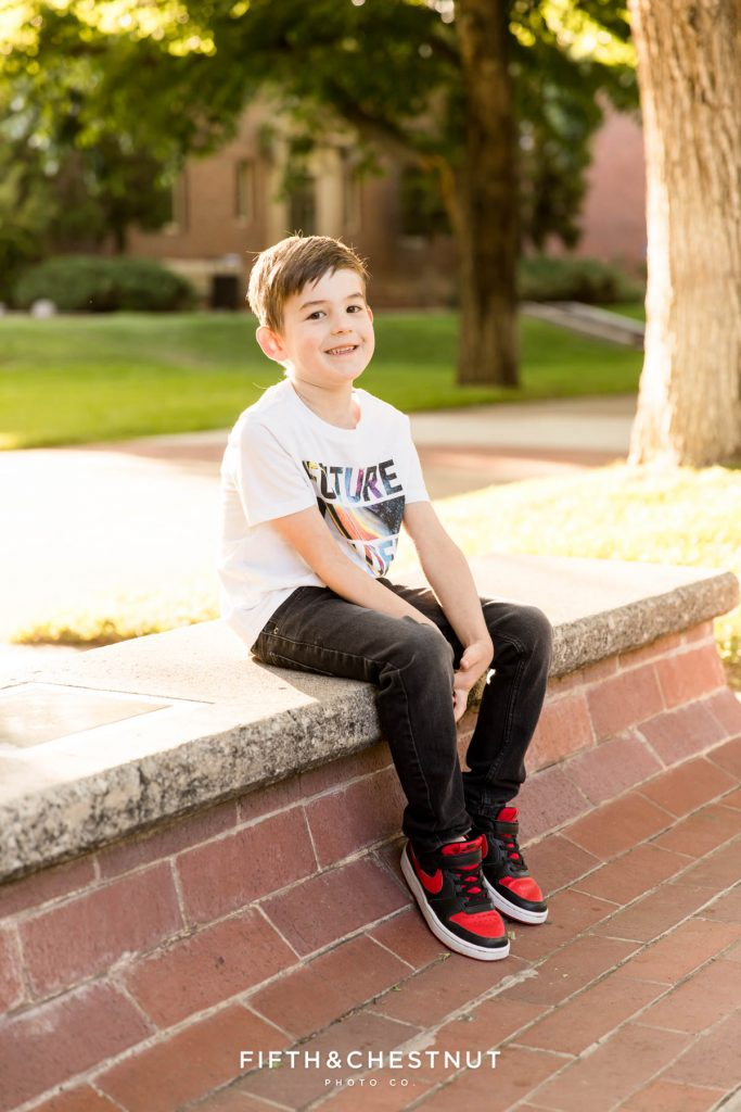 A. young boy smiles as he sits on a bench at UNR
