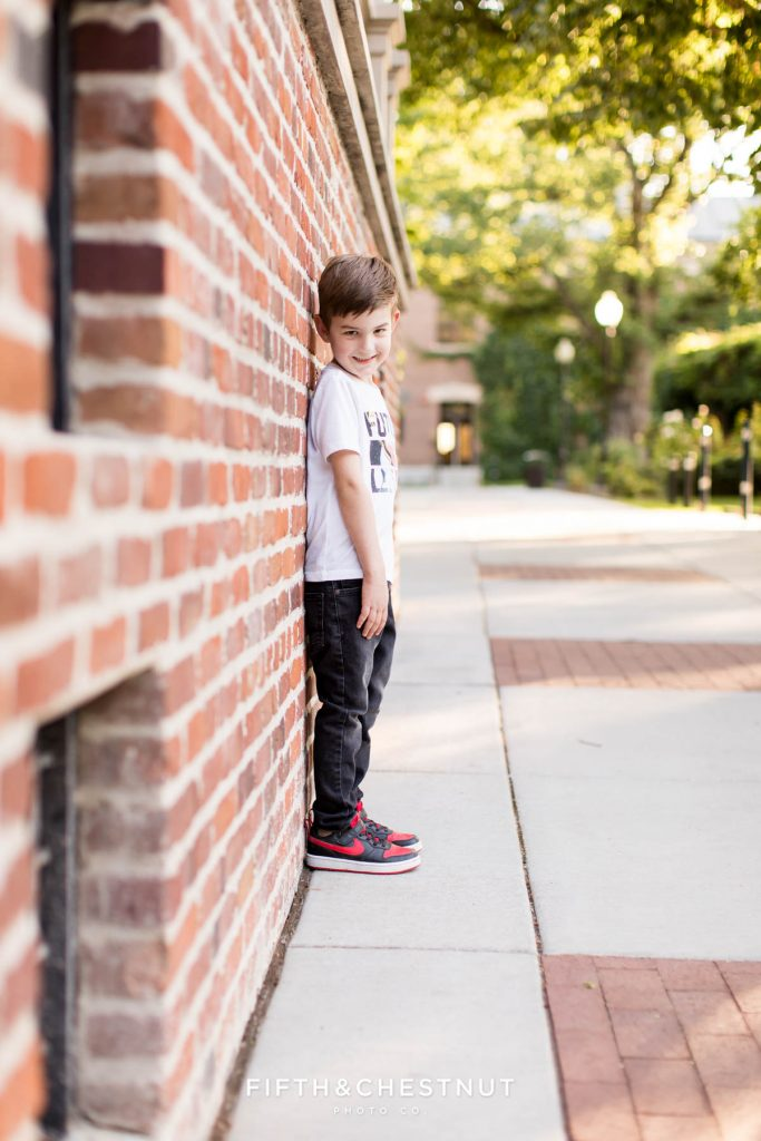 A boy leans on a brick wall at UNR for his child portraits in Reno, NV