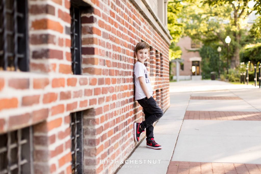 A boy leans on a brick wall with his hands in his pockets for reno child portraits at UNR