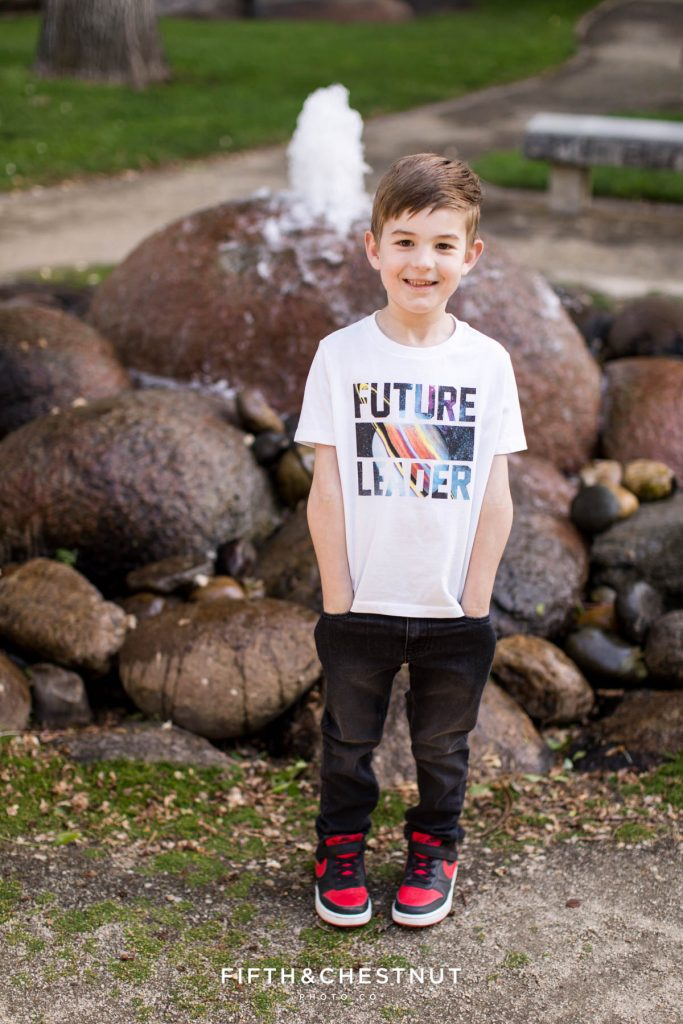 """A boy wearing a shirt that says """"Future Leader"""" with an image of Saturn on it smiles with his hands in his pockets at UNR"""