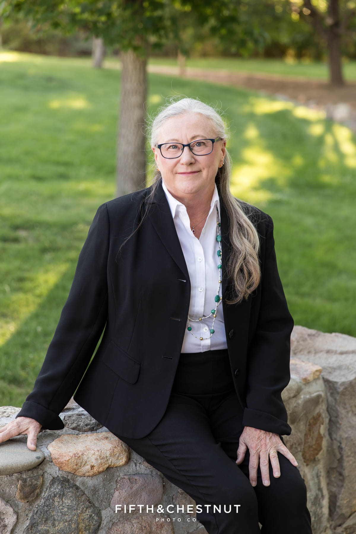 woman sitting on a stone wall wearing a black suit jacket for corporate portraits in the park